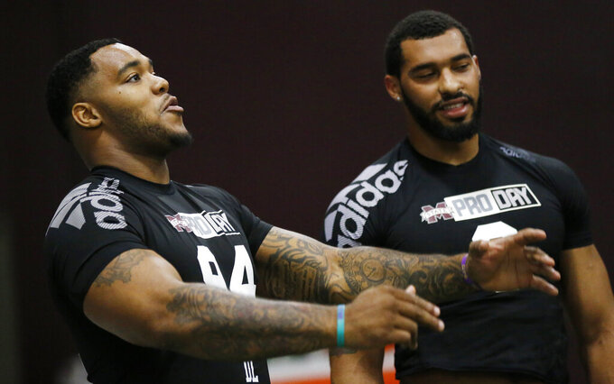 Former Mississippi State defensive players Jeffery Simmons, left, and Montez Sweat, joke around during Pro Day at the university, as other players were being tested by NFL football scouts and coaches, Wednesday, March 27, 2019, in Starkville, Miss. Sweat ran some agility drills, while Simmons stayed on the sidelines as he recovers from a leg injury. (AP Photo/Rogelio V. Solis)