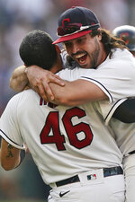 Cleveland Indians' Austin Hedges, right, hugs Rene Rivera after they defeated the Seattle Mariners in 10 innings in a baseball game, Saturday, June 12, 2021, in Cleveland. (AP Photo/Tony Dejak)