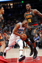 Charlotte Hornets guard Kemba Walker (15) drives against Atlanta Hawks center Dewayne Dedmon (14) during the second half of an NBA basketball Saturday, Feb. 9, 2019, in Atlanta. Charlotte won 129-120. (AP Photo/John Bazemore)