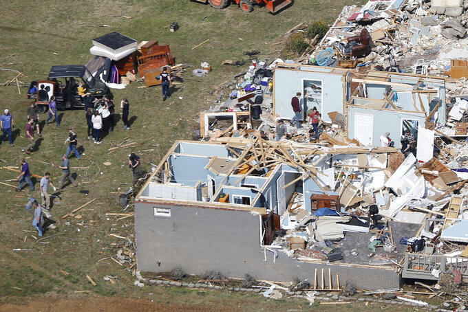 People work to salvage items Tuesday, March 3, 2020, near Cookeville, Tenn. Tornadoes ripped across Tennessee early Tuesday, shredding more than 140 buildings and burying people in piles of rubble and wrecked basements.  (AP Photo/Mark Humphrey)