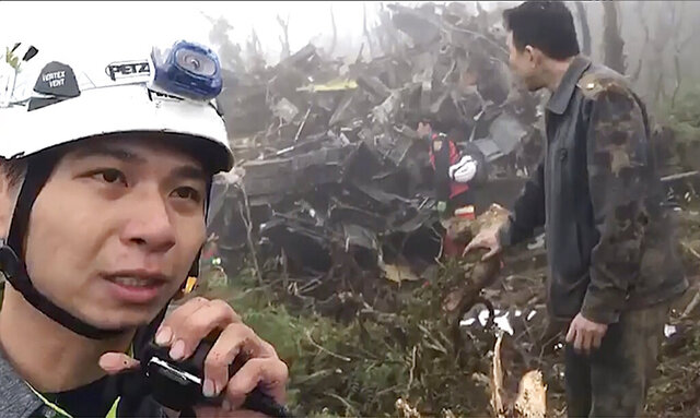 In this image made from video, emergency teams work at the crash site of a military helicopter in the mountains of Yilan, north eastern Taiwan, Thursday, Jan. 2, 2020. The defense ministry has confirmed Taiwan's top military officer Gen. Shen Yi-ming and others were killed in a crash of an air force helicopter. (Yilan Fire Bureau via AP)