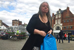 Julia Barber walks through the marketplace of Boston, England, Saturday Sept. 7, 2019. Three years ago, almost 76% of voters in this eastern England town opted, against the government's advice, to leave the European Union, the highest pro-Brexit vote in the U.K. With Britain's departure delayed and politicians deadlocked, Bostonians now feel frustration, fatigue and even fury. (AP Photo/Jeffrey Schaeffer)