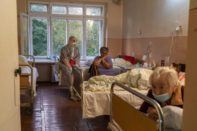 A medical worker speaks to a coronavirus patient at a hospital in Stebnyk, Ukraine, on Tuesday, Sept. 29 2020. As coronavirus cases increase, every bed in the hospital in this city in western Ukraine is in use and its chief doctor is watching the surge with alarm and anguish. (AP Photo/Evgeniy Maloletka)