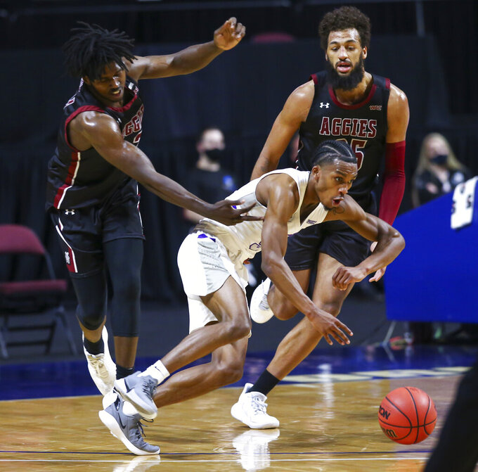 New Mexico State's Donnie Tillman, left, fouls Grand Canyon's Mikey Dixon during the second half of an NCAA college basketball game for the championship of the Western Athletic Conference men's tournament Saturday, March 13, 2021, in Las Vegas. (AP Photo/Chase Stevens)