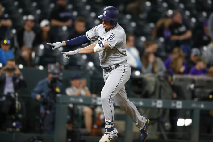 San Diego Padres' Hunter Renfroe celebrates as he circles the bases after hitting a two-run home run off Colorado Rockies relief pitcher Jairo Diaz in the 12th inning of a baseball game, Friday, June 14, 2019, in Denver. The Padres won 16-12. (AP Photo/David Zalubowski)