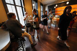 Visitors eat snacks and drink water during a media preview for the Sazerac house, in New Orleans, Tuesday, Sept. 10, 2019. Visitors to New Orleans who want to learn more about cocktails will soon have a new place to go. No, it's not another bar. The Sazerac House is a six-story building on the city's famed Canal Street owned by the Sazerac Company, a Louisiana-based spirits maker, featuring the signature New Orleans drink called the Sazerac.Tasting is encouraged, and in addition to free samples given to visitors, there will also be special classes and tastings offered daily. (AP Photo/Gerald Herbert)