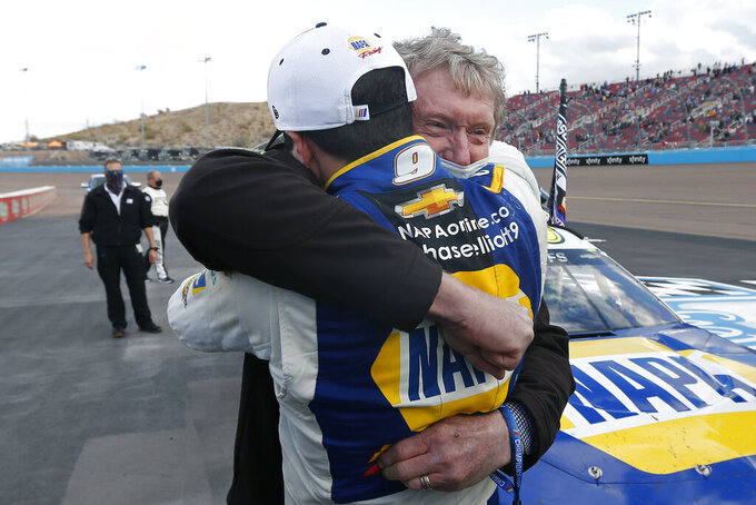 Chase Elliott (9) hugs his father Bill Elliott after winning the season championship during the NASCAR Cup Series auto race at Phoenix Raceway, Sunday, Nov. 8, 2020, in Avondale, Ariz. Bill is a former Cup Series champion. (AP Photo/Ralph Freso)