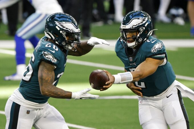 Philadelphia Eagles running back Miles Sanders (26) takes the hand off from quarterback Jalen Hurts (2) in the first half of an NFL football game against the Dallas Cowboys in Arlington, Texas, Sunday, Dec. 27. 2020. (AP Photo/Ron Jenkins)