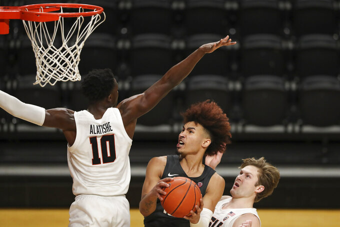 Washington State's Isaac Bonton drives to the basket in between Oregon State's Warith Alatishe (10) and Zach Reichle during the second half of an NCAA college basketball game in Corvallis, Ore., Saturday, Feb. 6, 2021. (AP Photo/Amanda Loman)