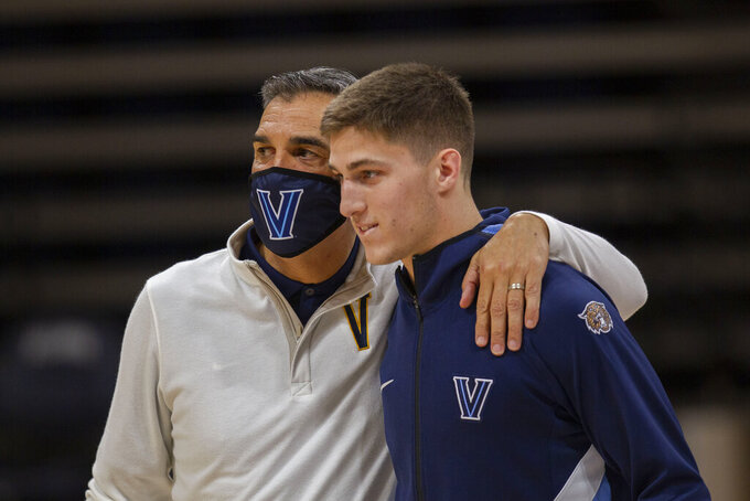 FILE - Villanova head coach Jay Wright, left, and guard Collin Gillespie are shown before an NCAA college basketball game against Creighton in Villanova, Pa., in this Wednesday, March 3, 2021, file photo. Villanova has dominated the Big East over the last decade under the guidance of coach Jay Wright. The fourth-ranked Wildcats were the unanimous choice to win the conference in a preseason coaches poll released Tuesday, Oct. 19, 2021. Villanova is led by guard Collin Gillespie, who was the coaches' pick for preseason player of the year.  (AP Photo/Laurence Kesterson, File)