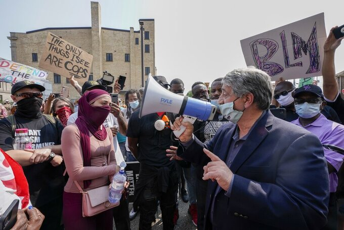 Kenosha Mayor John Antaramian, right, speaks to protesters using a megaphone, Monday, Aug. 24, 2020, in Kenosha, Wis. Kenosha police shot a man Sunday evening, setting off unrest in the city after a video appeared to show the officer firing several shots at close range into the man's back. (AP Photo/Morry Gash)