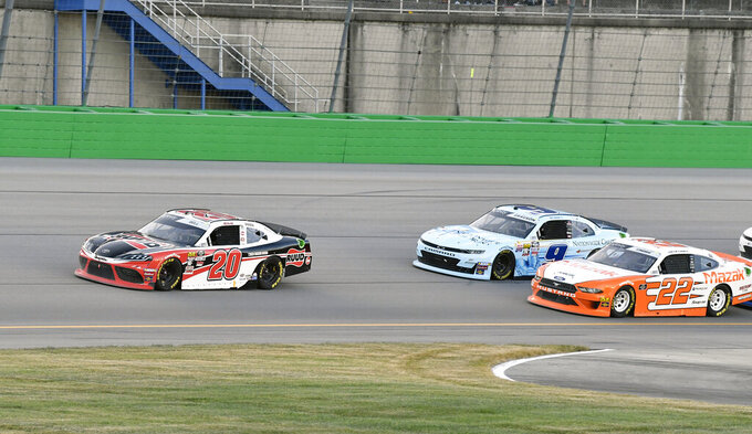 Christopher Bell (20) pulls away from Austin Cindric (22) and Noah Gragson (9) following a restart during the NASCAR Xfinity Series auto race at Kentucky Speedway in Sparta, Ky., Friday, July 12, 2019. (AP Photo/Timothy D. Easley)