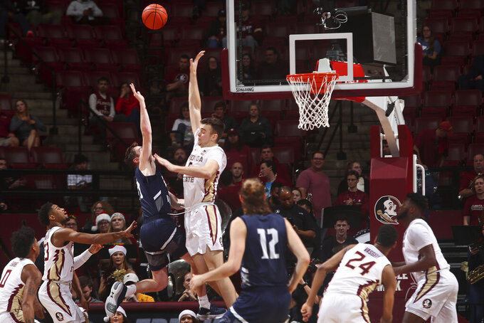 North Florida guard/forward Garrett Sams (11) makes a shot as he is fouled by Florida State center Balsa Koprivica (5) in the second half of an NCAA college basketball game in Tallahassee, Fla., Tuesday, Dec. 17, 2019. Florida State won 98-81. (AP Photo/Phil Sears)