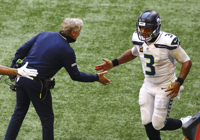 Seattle Seahawks quarterback Russell Wilson gets five from head coach Pete Carroll after tossing a touchdown pass to wide receiver DK Metcalf during an NFL football against the Atlanta Falcons during the third quarter Sunday, Sept. 13, 2020, in Atlanta. (Curtis Compton/Atlanta Journal-Constitution via AP)