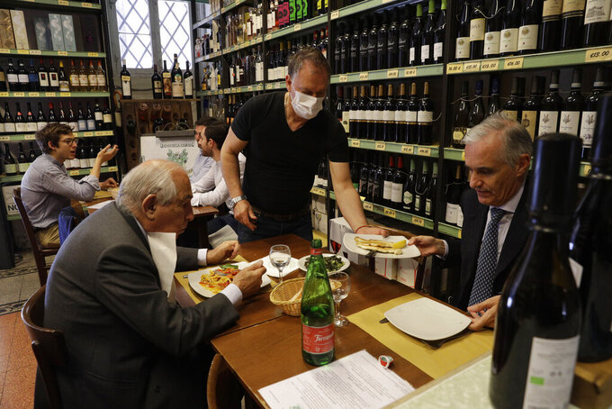 People gather inside a restaurant in downtown Rome, Tuesday, June 1, 2021. Starting Tuesday, customers were again allowed to access bars and restaurants, that were previously only permitted to serve outside or prepare for takeaway because of Covid restrictions. (AP Photo/Gregorio Borgia)