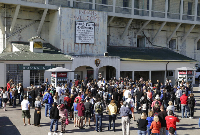 """FILE - In this Oct. 17, 2013, file photo, a National Park Service ranger welcomes visitors to Alcatraz Island in San Francisco. Alcatraz Island will reopen its outdoor areas to the public next week after being closed for five months due to the pandemic. The Mercury News reports Thursday, Aug. 13, 2020, the island that once housed Al Capone and George """"Machine Gun"""" Kelly will reopen Monday but will be an outdoor-only experience, to reduce the risk of spreading COVID-19. (AP Photo/Eric Risberg, File)"""
