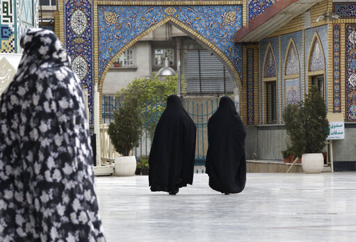 Head-to-toe veiled Iranian women walk at the shrine of Saint Saleh in northern Tehran, Iran, Tuesday, April 6, 2021.   (AP Photo/Vahid Salemi)