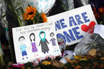 A message card is placed at a collection of flowers left at the Botanical Gardens in Christchurch, New Zealand, Saturday, March 16, 2019. New Zealand's stricken residents reached out to Muslims in their neighborhoods and around the country on Saturday, in a fierce determination to show kindness to a community in pain as a 28-year-old white supremacist stood silently before a judge, accused in mass shootings at two mosques that left dozens of people dead. (AP Photo/Vincent Thian)