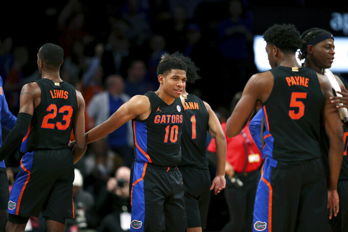 Florida guard Noah Locke (10) celebrates with teammates after the team defeated Providence in an NCAA college basketball game at Barclays Center, Tuesday, Dec. 17, 2019, in New York. Florida won 83-51. (AP Photo/Michael Owens)