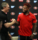 San Francisco 49ers general manager John Lynch, left, shakes hands with Kwon Alexander following an NFL news conference Thursday, March 14, 2019, in Santa Clara, Calif. (AP Photo/Ben Margot)