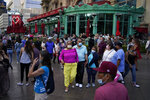 People walk along the Las Vegas Strip, Saturday, April 24, 2021, in Las Vegas. Las Vegas is bustling again after casino capacity limits were raised Saturday, May 1, to 80% and person-to-person distancing dropped to 3 feet (0.9 meters). (AP Photo/John Locher)