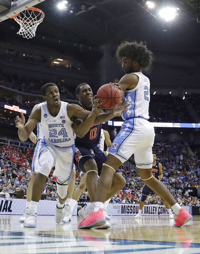 Auburn's Horace Spencer (0) reaches for the ball between North Carolina's Kenny Williams (24) and Coby White during the second half of a men's NCAA tournament college basketball Midwest Regional semifinal game Friday, March 29, 2019, in Kansas City, Mo. (AP Photo/Charlie Riedel)