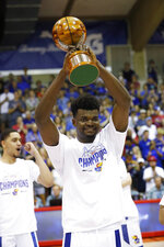 Kansas center Udoka Azubuike raises the MVP trophy after he and guard Devon Dotson shared the award, Wednesday, Nov. 27, 2019, in Lahaina, Hawaii. Kansas defeated Dayton in 90-84 in overtime. (AP Photo/Marco Garcia)