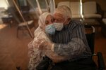 In this Monday, June 22, 2020 photo, Dolores Reyes Fernández, 61, hugs her father José Reyes Lozano, 87, for the first time in nearly four months as visits resume to a nursing home in Barcelona, Spain. At the height of Spain's coronavirus outbreak, nursing homes locked out visitors to try to shield their residents from the virus killing so many elderly people. One home in Barcelona has allowed family visits to resume through plastic screens. (AP Photo/Emilio Morenatti)