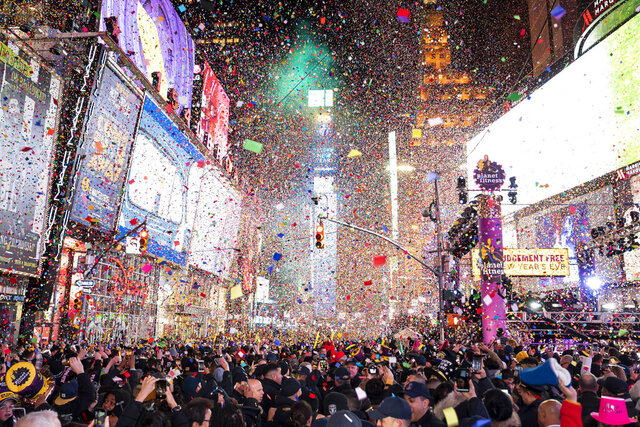 FILE - In this Jan. 1, 2020, file photo, confetti falls at midnight on the Times Square New Year's Eve celebration in New York. If ever a year's end seemed like cause for celebration, 2020 might be it. Yet the coronavirus scourge that dominated the year is also looming over New Year's festivities and forcing officials worldwide to tone them down. (Photo by Ben Hider/Invision/AP, File)