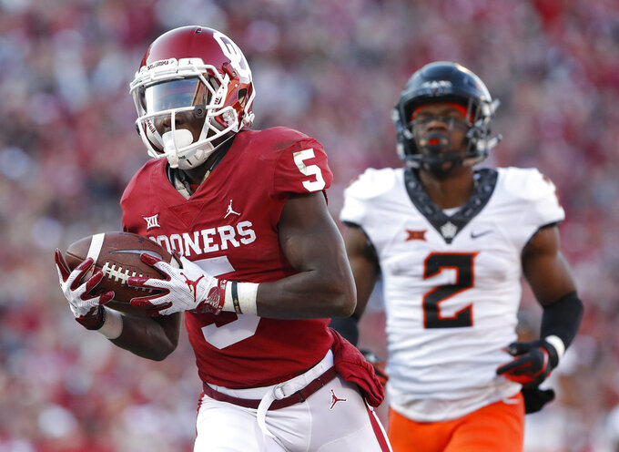FILE - In this Nov. 10, 2018, file photo, Oklahoma wide receiver Marquise Brown (5) runs in for a touchdown ahead of Oklahoma State cornerback Tanner McCalister (2) in the second quarter of an NCAA college football game in Norman, Okla. The Sooners and Longhorns are loaded with playmakers on the outside, but the ones with the best case to be All-Americans are Oklahoma's Marquise Brown and Texas' Lil'Jordan Humphrey. (AP Photo/Alonzo Adams, File)