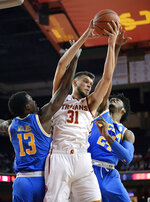 Southern California forward Nick Rakocevic, center, grabs a rebound away from UCLA guard Kris Wilkes, left, and guard Jalen Hill during the first half of an NCAA college basketball game Saturday, Jan. 19, 2019, in Los Angeles. (AP Photo/Mark J. Terrill)