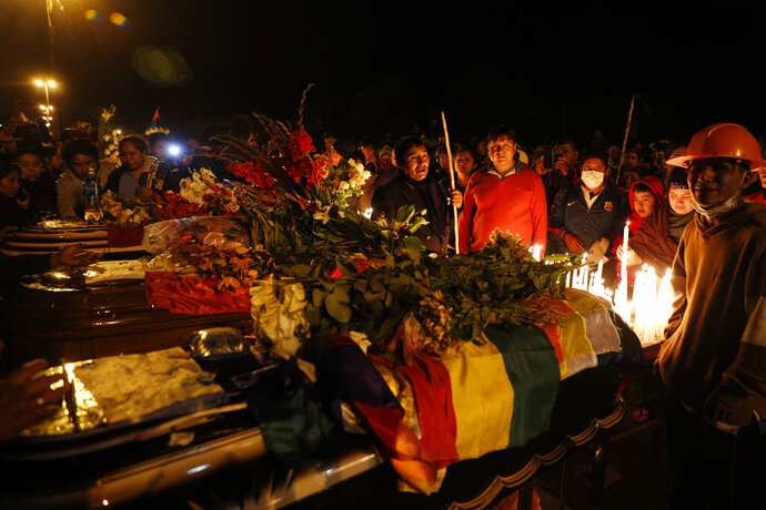 Mourners gather around coffins of backers of former President Evo Morales killed during clashes with security forces in Sacaba, Bolivia, Friday, Nov. 15, 2019. Bolivian security forces clashed with Morales' backers leaving at least five people dead, dozens more injured and escalating the challenge to the country's interim government to restore stability. (AP Photo/Juan Karita)