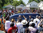 FILE - The hearse carrying the body of Muhammad Ali passes in front of his boyhood home, top center, during his funeral procession in Louisville, Ky., in this Friday, June 10, 2016, file photo. Five years after his death, residents, as well as Ali's daughter, Rasheda Ali, look back at the legacy of the boxer and the ways the people of Louisville have come together since his passing. (AP Photo/Mark Humphrey, File)