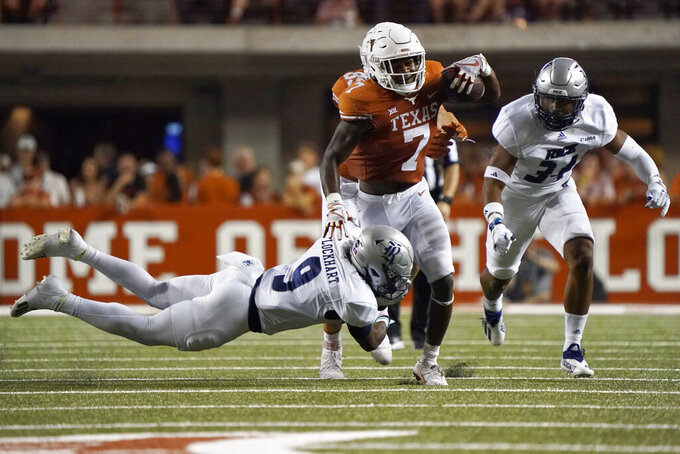 Texas running back Keilan Robinson (7) is hit by Rice safety Kirk Lockhart (9) during the second half of an NCAA college football game Saturday, Sept. 18, 2021, in Austin, Texas. (AP Photo/Chuck Burton)