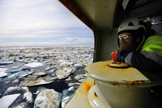FILE - In this July 16, 2017, file photo, Jussi Mikkotervo looks out from the bow of the Finnish icebreaker MSV Nordica as it sails through ice floating on the Beaufort Sea off the coast of Alaska while traversing the Arctic's Northwest Passage. Salla, Finland has launched a firmly tongue-in-cheek bid for the 2032 Summer Olympics, hoping to use its campaign to raise awareness about climate change and global warming. (AP Photo/David Goldman, File)