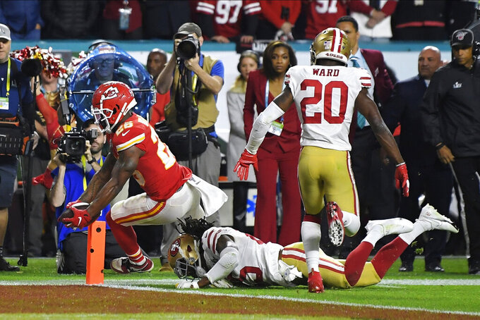 Kansas City Chiefs' Damien Williams, left, crosses the goal line for a touchdown against the San Francisco 49ers during the second half of the NFL Super Bowl 54 football game Sunday, Feb. 2, 2020, in Miami Gardens, Fla. (AP Photo/Mark J. Terrill)