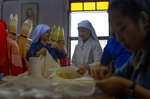 In this Friday, Nov. 8, 2019, photo, seamstresses from the Congregation of the Sacred Heart of Jesus Sisters of Bangkok snip and sew at a Catholic preparatory school in Bangkok, Thailand. A 11-member team of Sisters have been racing the clock, 10 hours a day, stitching almost 200 ceremonial garments for Pope Francis and accompanying bishops for Pope Francis four-day visit to Thailand later this month. (AP Photo/Gemunu Amarasinghe)
