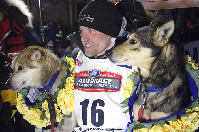 FILE - In this March 15, 2016, file photo, Dallas Seavey poses with his lead dogs Reef, left, and Tide after finishing the Iditarod Trail Sled Dog Race in Nome, Alaska. Iditarod officials have cleared a four-time champion of any wrongdoing in a dog-doping scandal that followed the sled dog race last year. Officials for the 1,000-mile (1,610 kilometer) Iditarod Trail Sled Dog Race issued a statement this week absolving Seavey of any involvement in the drugging of his dogs, the Anchorage Daily News reported. (AP Photo/Mark Thiessen, File)