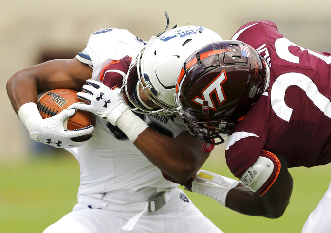 Old Dominion running back Blake Watson, left, is tackled by Virginia Tech defender Chamarri Conner, right,in the first half of an NCAA college football game  in Blacksburg Va,. Saturday, Sept. 7, 2019. (Matt Gentry/The Roanoke Times via AP)