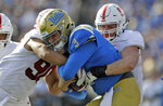 UCLA quarterback Wilton Speight (3) is tackled by Stanford defensive end Dylan Jackson, right, and linebacker Gabe Reid during the first half of an NCAA college football game Saturday, Nov. 24, 2018, in Pasadena, Calif. (AP Photo/Marcio Jose Sanchez)