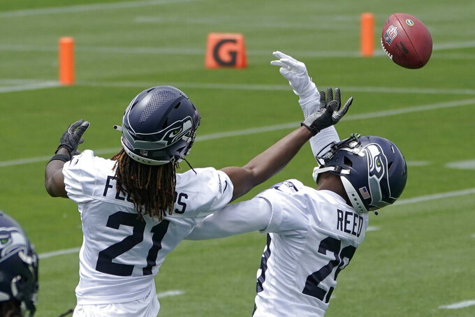 Seattle Seahawks cornerbacks Tre Flowers, left, and D.J. Reed, right, reach for the football during a drill at NFL football practice Tuesday, June 15, 2021, in Renton, Wash. (AP Photo/Ted S. Warren)