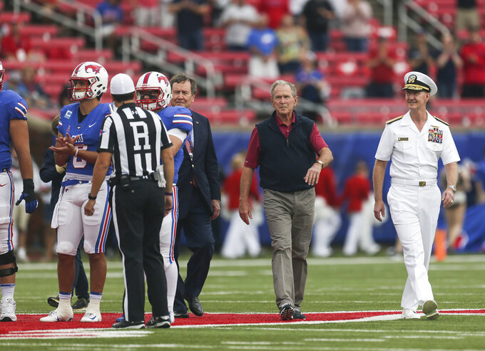 Former President George W. Bush makes his way onto the field for the coin toss before an NCAA college football game between Navy and SMU, Saturday, Sept. 22, 2018, at Gerald J. Ford Stadium in Dallas. (Ryan Michalesko/The Dallas Morning News via AP)