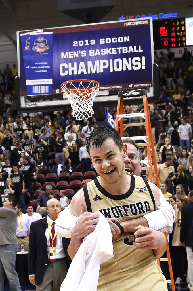 Wofford guard Fletcher Magee (3) receives a hug after his team defeated UNC-Greensboro 70-58 for the Southern Conference tournament championship, Monday, March 11, 2019, in Asheville, N.C. Magree is the Most Valuable Player of the game. (AP Photo/Kathy Kmonicek)