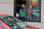 A barista serves up a drink in the drive through lane at a Starbucks Coffee store in south Seattle, Tuesday, Oct. 27, 2020. Starbucks saw faster-than-expected recovery in the U.S. and China in its fiscal fourth quarter, giving it confidence as it heads into the holiday season. (AP Photo/Ted S. Warren)