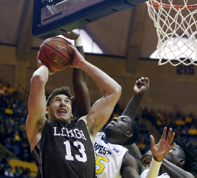 Lehigh center James Karnik (13) is blocked by West Virginia forward Lamont West (15) during the first half of an NCAA college basketball game Sunday, Dec. 30, 2018, in Morgantown, W.Va. (AP Photo/Raymond Thompson)