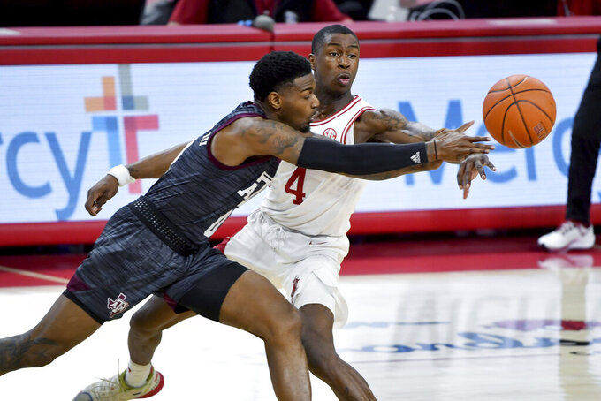 Texas A&M guard Jay Jay Chandler (0) tries to get past Arkansas guard Davonte Davis (4) during the first half of an NCAA college basketball game in Fayetteville, Ark., Saturday, March 6, 2021. (AP Photo/Michael Woods)
