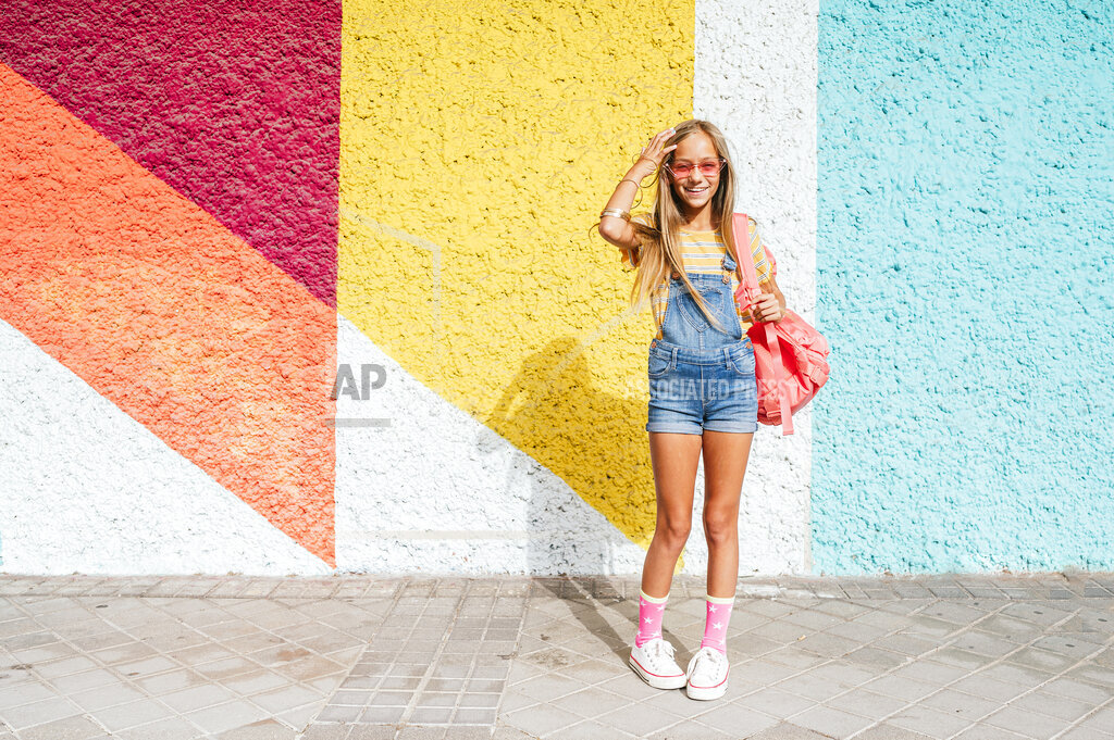 Smiling girl with backpack standing on footpath