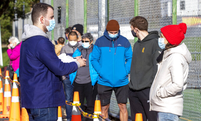 People queue outside a COVID-19 testing station in Wellington, New Zealand, Thursday, June 24, 2021. After enjoying nearly four months without any community transmission of the coronavirus, New Zealanders were on edge Wednesday after health authorities said an infectious traveler from Australia had visited over the weekend. (Mark Mitchell/NZ Herald via AP)