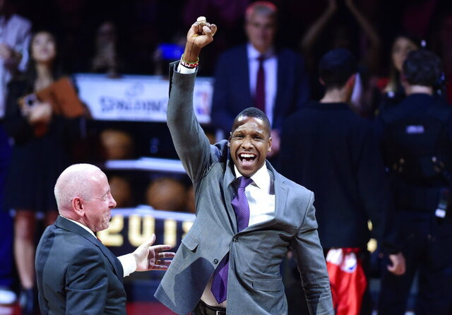 FILE - Toronto Raptors president Masai Ujiri receives his 2019 NBA basketball championship ring from Larry Tanenbaum, chairman of Maple Leaf Sports & Entertainment, before the Raptors played the New Orleans Pelicans in Toronto, Tuesday, Oct. 22, 2019.  A new video released by the attorneys of Ujiri appears to show an Alameda County sheriff's deputy initially shoved him twice leading to an altercation moments after his team had defeated the Golden State Warriors in last year's NBA championship. (Frank Gunn/The Canadian Press via AP,File)