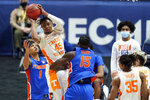 Tennessee's Keon Johnson (45) passes the ball away from Florida defenders Tre Mann (1) and Osayi Osifo (15) in the second half of an NCAA college basketball game in the Southeastern Conference Tournament Friday, March 12, 2021, in Nashville, Tenn. (AP Photo/Mark Humphrey)